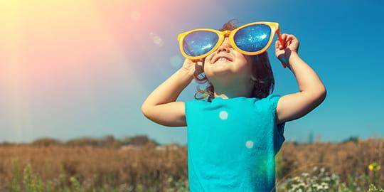 Kind mit übergroßer Brille schaut freudig in den Himmel