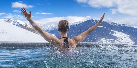 Frau schaut aus Pool in die österreichische Umgebung