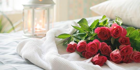 Rote Rosen liegen auf dem Hotelbett