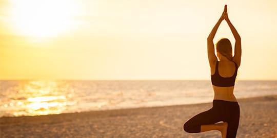 Frau macht Yoga am Strand bei Sonnenaufgang