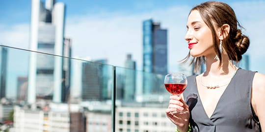 Frau schaut zufrieden von der Dachterrasse ihres Frankfurter Hotels