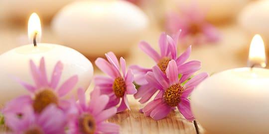 Kerzen und Blumen begleiten eine sinnliche Massage