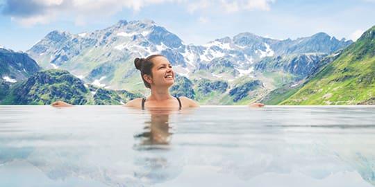 Frau in Therme genießt Aussicht auf Bergpanorama