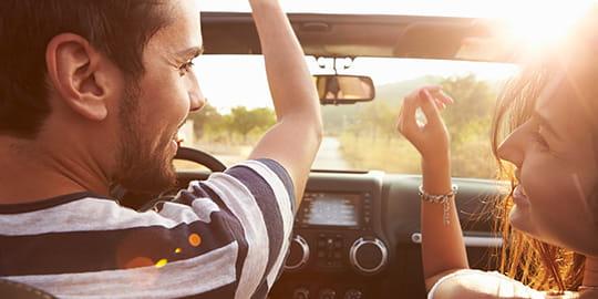 Pärchen im Auto mit Vorfreude auf den Kurzurlaub