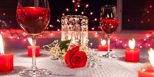 Romantisch gedeckter Tisch mit Rosen und Rotwein